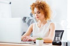 Attraktiv affärskvinna som i regeringsställning arbetar med bärbara datorn royaltyfria bilder
