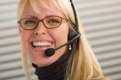 attraktiv affärskvinnahörlurar med mikrofontelefon Arkivbild