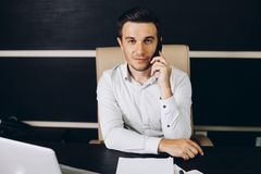 Attraktiv affärsman i smart sammanträde för tillfälliga kläder på hans arbetsplats i regeringsställning som rymmer en smart telef Royaltyfri Foto