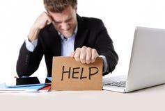 Attraktiv affärsman som arbetar i spänning på tecknet för papp för datorinnehavhjälp Royaltyfri Foto