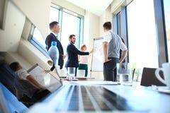 Attraktiv affärsman som ger en presentation till hans anställda i kontoret arkivbild