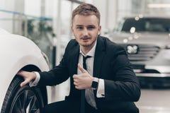 Attraktiv affärsman som köper den nya bilen på återförsäljaren fotografering för bildbyråer