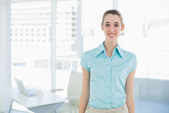 Attraktiv affärskvinna som bär den blåa blusen som poserar i hennes kontor Royaltyfri Fotografi
