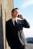 Attraktiv affärsman som utomhus talar på mobiltelefonen Arkivbild