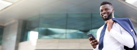 Attraktiv afrikansk affärsman som rymmer hans telefon, medan stå nära en våningsbyggnad och se rakt framåt arkivfoton