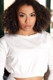 Attraktiv afrikansk amerikanflickastående i den vita tröjan Arkivbild