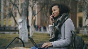 Attraktiv afrikansk amerikanstudentflicka som utomhus talar hennes telefonsammanträde på bänk med bärbar datordatoren arkivfilmer
