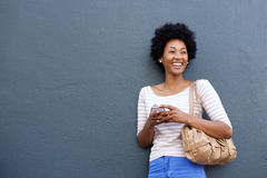 Attraktiv afrikansk kvinna som ler med mobiltelefonen och påsen arkivfoton