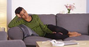 Attraktiv afrikansk kvinna som sover på soffan Fotografering för Bildbyråer