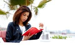 Attraktiv afro--amerikan kvinnlig läs- fascinerande bok, medan sitta på terrassen av coffee shop royaltyfria bilder