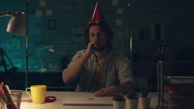 Attraktiv allvarlig kontorsarbetare som hårt sent arbetar på hans kabinett på natten, drinkte och programmerar något på hans arkivfilmer