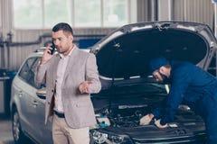 Attraktiv allvarlig upptagen ägare av en bil, som får att värdera av arkivbild