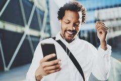 Attraktiv amerikansk afrikansk svart man som lyssnar till musik med hörlurar i stads- bakgrund Lyckliga män som använder smartpho Royaltyfri Foto