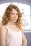 Attraktiv anseendeframdel för ung kvinna av fönstret Royaltyfria Bilder