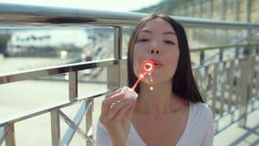 Attraktiv asiatisk flicka som blåser bubblor som står på bron stock video