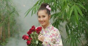 Attraktiv asiatisk kvinna i traditionell dräkt med en bukett av blommor av röda rosor som ser till kameran och ler på stock video