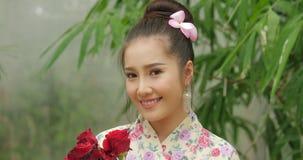 Attraktiv asiatisk kvinna i traditionell dräkt med en bukett av blommor av röda rosor som ser till kameran och ler på lager videofilmer