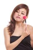 Attraktiv asiatisk kvinna som applicerar smink Arkivbild