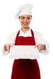 Attraktiv asiatisk kvinnlig kock som levererar pizza royaltyfri bild