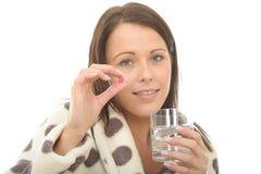 Attraktiv avkopplad ung kvinna som dåligt känner sig, och opasslig tagande medicin Royaltyfri Bild
