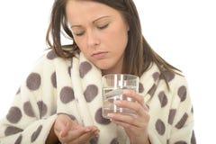 Attraktiv avkopplad ung kvinna som dåligt känner sig, och opasslig tagande medicin Royaltyfri Fotografi