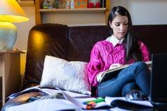 Attraktiv avläsning för brunettkvinnastudent som flickaktigt studerar i henne rum Arkivfoton