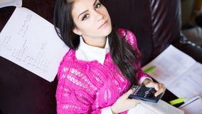 Attraktiv avläsning för brunettkvinnastudent som flickaktigt studerar i henne rum Royaltyfri Bild