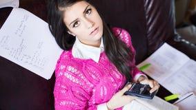 Attraktiv avläsning för brunettkvinnastudent som flickaktigt studerar i henne rum Arkivfoto