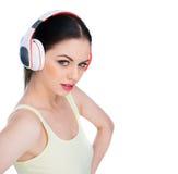 Attraktiv bärande hörlurar för ung kvinna royaltyfri bild