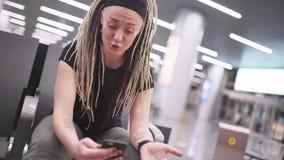 Attraktiv blogger för ung kvinna med dreadlocks genom att använda telefonen på flygplatsen Stående av den härliga hipsterkvinnan stock video