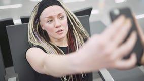 Attraktiv blogger för ung kvinna med dreadlocks genom att använda telefonen på flygplatsen Stående av den härliga hipsterkvinnan arkivfilmer