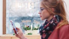Attraktiv blond flicka som använder hennes telefon för messaging, medan sitta i det centrala kafét Suddighetsbild Kvinnlig ståend lager videofilmer