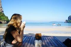 Attraktiv blond flicka som dricker kaffe vid stranden royaltyfri fotografi