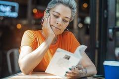 Attraktiv blond flickaläsebok på kafét arkivfoto