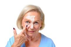 Attraktiv blond hög dam som applicerar skönhetsmedel Royaltyfri Foto