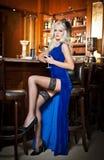 Attraktiv blond kvinna i elegant blått långt klänningsammanträde på stångstolen som rymmer ett exponeringsglas i hennes hand. Ursn Royaltyfri Bild