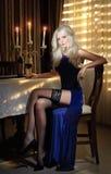 Attraktiv blond kvinna i elegant långt klänningsammanträde nära en tabell i en lyxig klassisk inre. Ursnygg blond modell Royaltyfri Fotografi