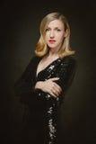 Attraktiv blond kvinna i en svart coctailklänning royaltyfri bild