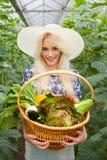 Attraktiv blond kvinna med en korg av grönsaker Royaltyfri Fotografi