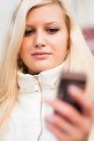 Attraktiv blond kvinna med mobiltelefonen Royaltyfri Fotografi
