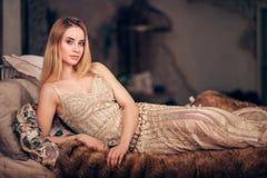 Attraktiv blond kvinna som bär den eleganta guld- klänningen som ligger på sängen på partiet för nytt år arkivbild