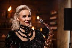 Attraktiv blond kvinna som har en jazzkonsert på hennes saxopone i en bar royaltyfria foton
