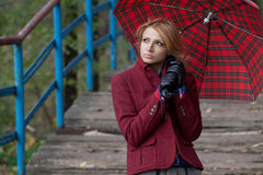 Attraktiv blond kvinna som poserar under ett rött paraply Arkivbild