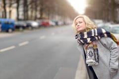 Attraktiv blond kvinna som väntar på en taxi eller en elevator arkivfoton