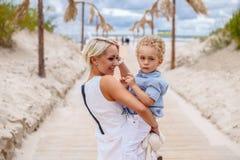 Attraktiv blond moter som rymmer hennes barn Royaltyfri Fotografi