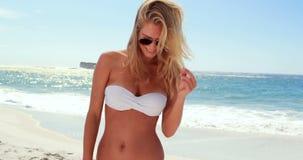 Attraktiv blondin med solglasögon på stranden lager videofilmer