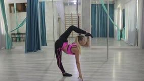 Attraktiv blondin som gör sträcka stammen, medan stå i sportklubba arkivfilmer