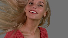 Attraktiv blondin som skakar hennes hår upp på grått bakgrundsslut upp lager videofilmer