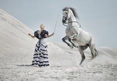 Attraktiv blondin som utbildar hästen Fotografering för Bildbyråer