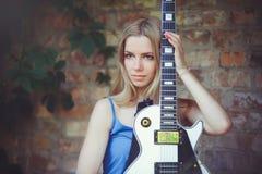 Attraktiv blygsam ung blond kvinna med en vit gitarr i handen som rymmer en väggbakgrund blyg och frågvis arkivbild